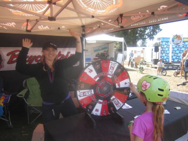 Alyse Weyman spins the Giant Wheel of goodies at the Bicycle Trip tent.