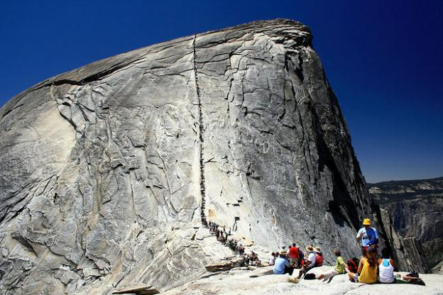 People lined up to climb the last 400 feet of Half Dome. Photo by HylgeriaK on Creative Commons.