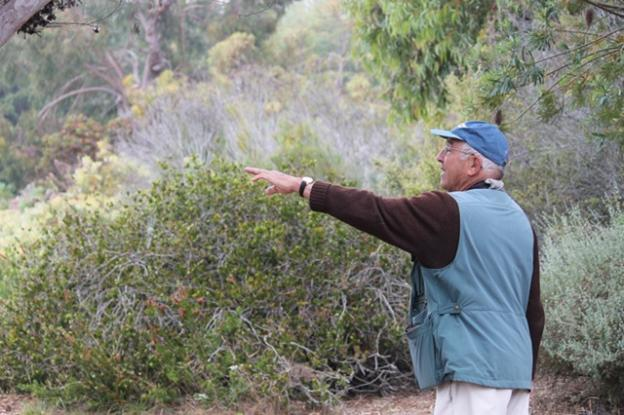 Retired UCSC professor and legendary local birder Todd Newberry points to the silken strands of an orb-weaving spider's creation.