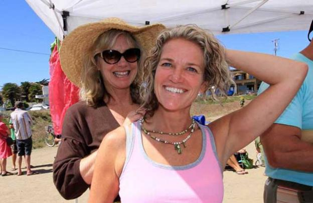 Heidi Nilson trying on her new necklace with the help of Kathy Julian.