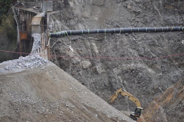 The river flows through a feeding tube lashed to the hillside as the San Clemente Dam is removed.