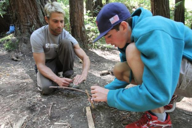 Assistant Adventure Out instructor Mark Maitland, left, looks on as a student assembles a fire bow.