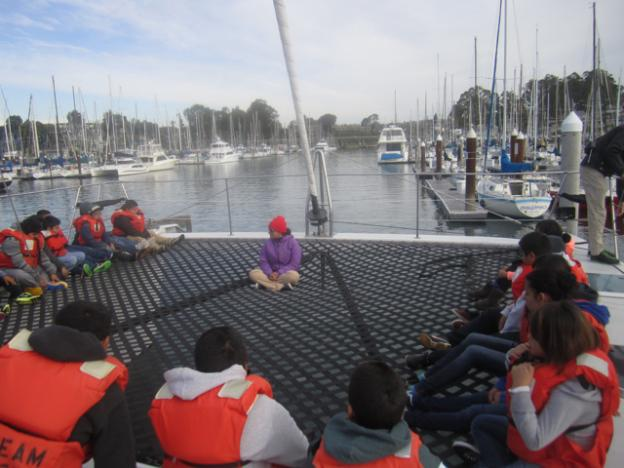 Celia Lara of O'Neill Sea Odyssey gives the students an orientation on the O'Neill Catamaran's mesh deck.