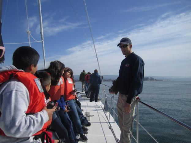 Instructor Adam Steckley gets the kids ready to use their compasses to locate the boat's position using landmarks like the Giant Dipper.
