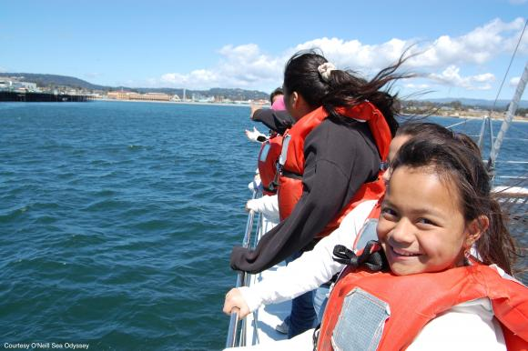 Smiling little girl on a boat, wearing a life jacket