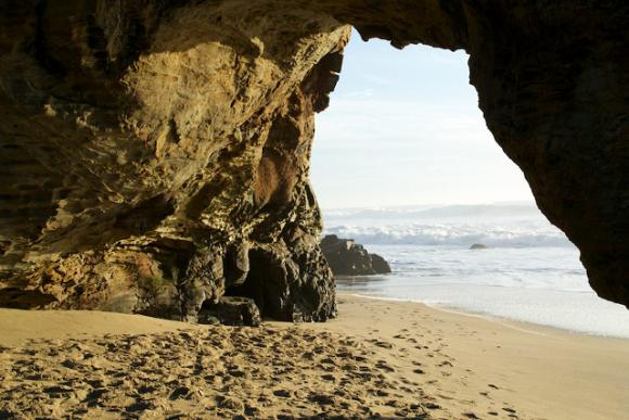 Duck through the hole in the wall at Panther Beach to get to a wide-open expanse of sand. Photo credit: Malikas99.