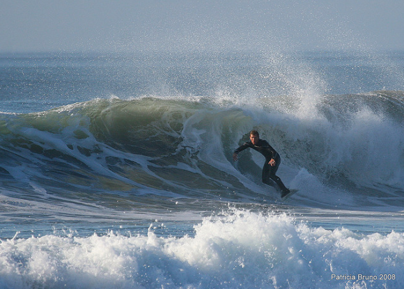 A guy in a wetsuit surfing a big, cold-looking wave in the afternoon. Photo credit: Patty Bruno.