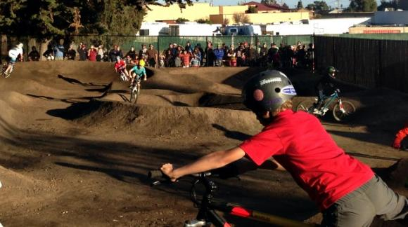 Bike groms lined up to take a turn on the new Westside pump track at the official ribbon-cutting on Saturday. Hanae Armitage photo.