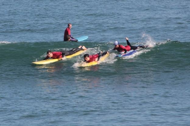 Surf instructor Nina Ke'alohi Dodge, in cap, pushes Pil Nam into a wave. Next to him Bragi Sveinsson paddles hard while Ryan Smith looks on. Chip Scheuer photo.