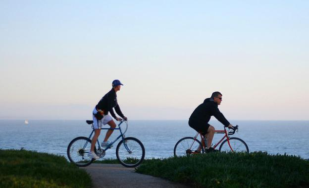 These West Cliff Drive riders will be able to pedal all the way to Coast Dairies soon (hopefully). Photo by Richard Masoner/CC.