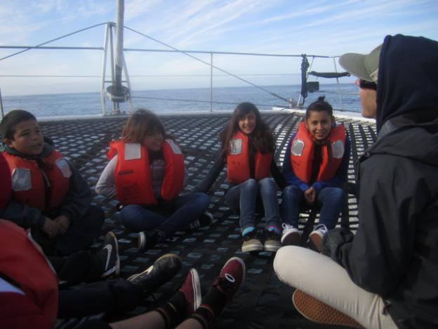 Students listen to Lauren Hanneman talking about marine ecosystems.