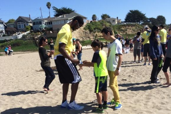 After the heavy lifting comes the care and feeding of fans. A Warriors player signs autographs at the March 15 Seabright beach cleanup. Photo by Alexa Lomberg.